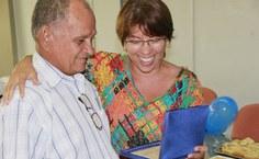 A coordenadora da Ascom, Simoneide Araújo, agradece a Manoel pelo seu trabalho nesses 33 anos e entrega-lhe a homenagem